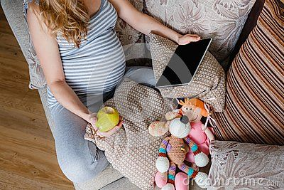 Pregnant woman resting on the sofa with a tablet PC. Pregnant concept.