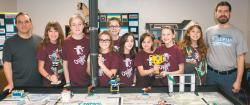 Members of Quaker UP! one of two Lego robotics teams that will represent Western New York at the 2017 FIRST Lego League World Festival in St. Louis in April, stand with coaches Dave Bogart, far left, and Russell Faust in their basement practice room in Bogart's home. From left are team members Elizabeth Faust, Ella Nenoff, Katie Bogart, Chloe Johnson, Catherine Lesh, Madeline Bogart, Kelly Thorpe and Amanda Faust.  Photo by Chuck Skipper Purchase color photos at www.BeeNews.com