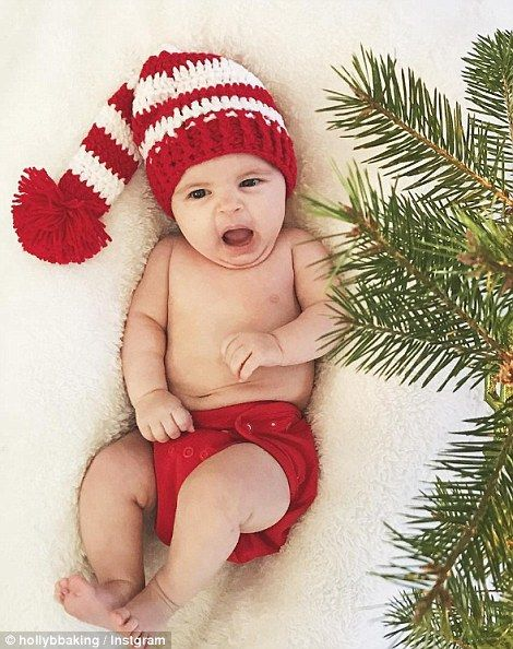 Having fun: One photo shows a baby pulling faces beside the Christmas tree