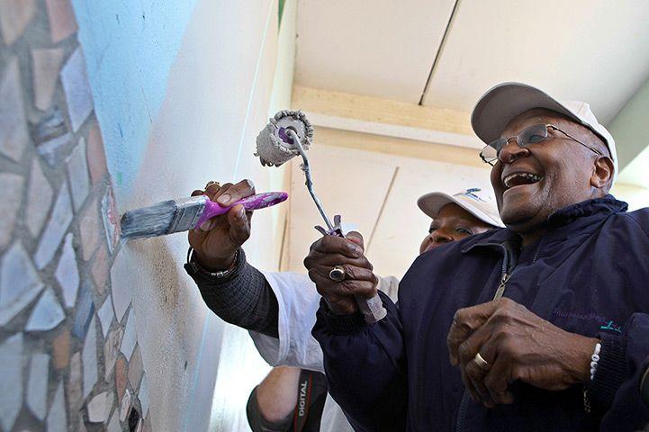 Mandela's birthday: Desmond Tutu paint a wall at the Marconi Beam Public Primary School