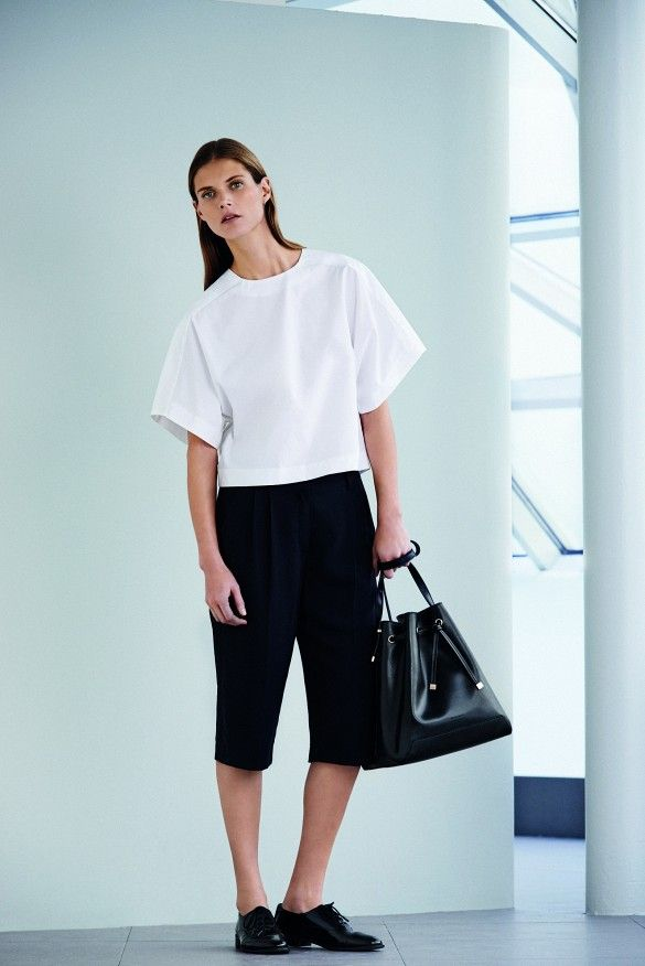 A cropped white short-sleeve blouse is paired with black knee-length shorts, oxfords, and a bucket bag