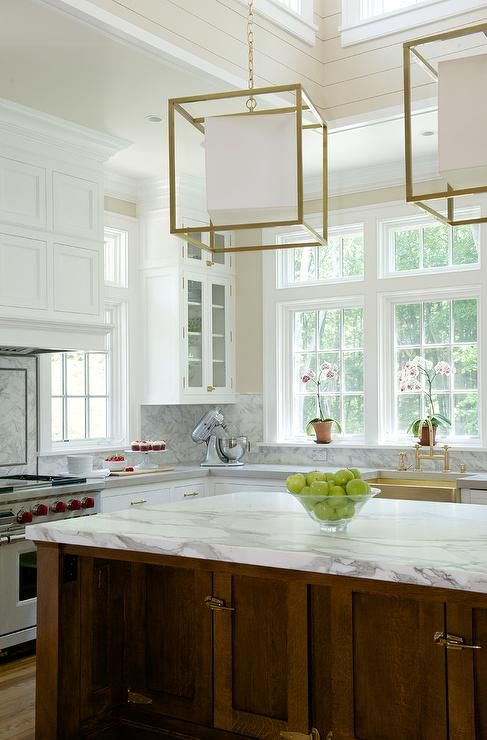 Stunning two tone kitchen features a white wainscoted vent hood fixed to a marble backsplash above a dual Wolf range located beside a window positioned above white shaker cabinets finished with brass hardware and a gray quartzite countertop complementing a marble backsplash.
