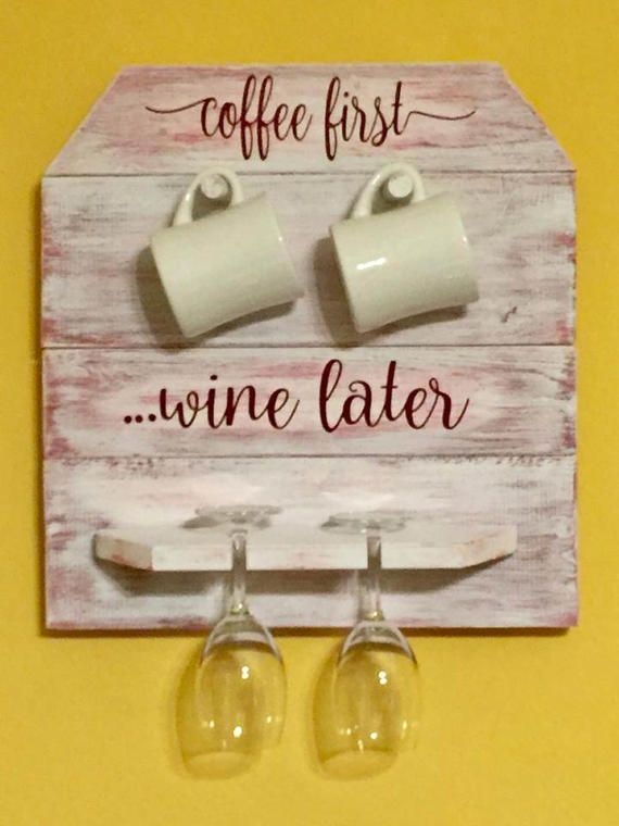 Shabby Chic Coffee Mug and Wine Glass Holder.... Coffee first, Wine later.  Perfect Home Decor for Coffee/Wine Bar! This Coffee Mug/Wine Glass Holder measures 17 wide by 18 tall and comes with hooks on back to hang. This is made of wood, painted and sealed. Accommodates two coffee mugs and 2 wine glasses. You also have the choice to customize with AM on top and PM on bottom or any other cute saying that would fit in the same space.  This is done with an antique white with maroon. Ca...