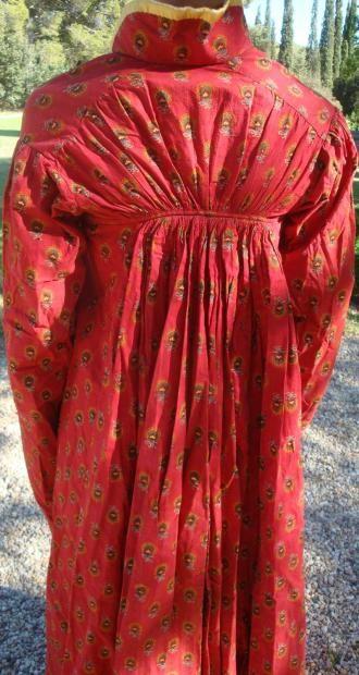 """Summer redingote of dyed """"Turkish red"""" cotton, from Provence, ca. 1812. Redingote d'été imprimée en rouge Andrinople, Provence, vers 1812 Robe redingote en coton imprimé* par enlevage de fleurons vert et jaune sur fond rouge Andrinople dit «rouge turc». Manches longues en tuyau de poële, col, ourlet, poignets et devants gansés de soie jaune pale, dos étroit monté à petites fronces sur taille haute, trois pattes de fermeture et boutons recouverts."""