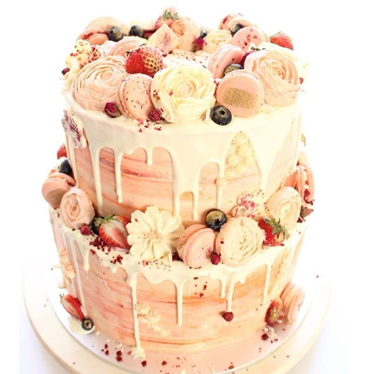 PINK & WHITE RED VELVET ROSE |  Two large tiers of red velvet sponge in ombré red tones, encased in a watercolour pink-coral buttercream. Surrounded with hand-piped buttercream flowers; in house rose-lychee & red velvet macarons; rose white chocolate cubes and gold dusted berries. The perfect cake for a Spring birthday