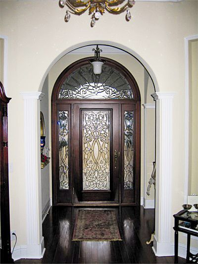 "Door Style DbyD-1031. This gorgeous Front Exterior Entry shows a Mahogany 36"" x 80"" Style ""F"" Door with Fluted Molding, Rosettes, Ledge and Dentil. The Sidelites are Mahogany 12"" x 80"" Style ""F"" Sidelites. The Front Exterior Entry is completed with a Mahogany Radius Transom. The Leaded Beveled Glass was built by Doors by Decora. The Hardware is Baldwin Springfield 6573-003. The stain color is Traditional Mahogany."