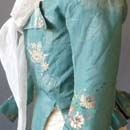 the turquoise taffeta silk woven with sprays of soft vermillion red, yellow, apricot, green and ivory and others of soft apricot and silver, with a silvery background lace effect weave, the front with turned back pointed revers and long pointed front, the sleeves with wrist slits, the back with pointed tail and a softly pleated skirt, lined with linen back neck to hem 17 in or 43 cm.