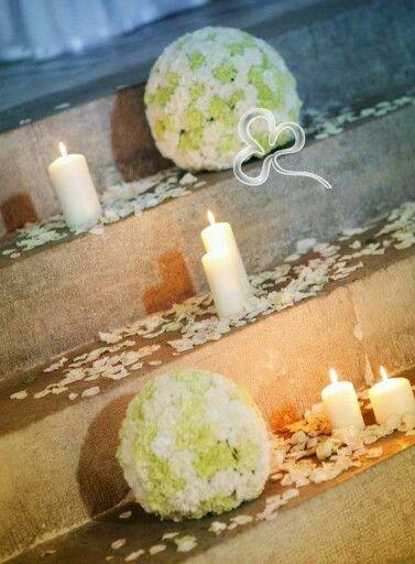 Sfere floreali in un delicato susseguirsi di white & green, morbida luce di candele accompagnano gli sposi all'altare