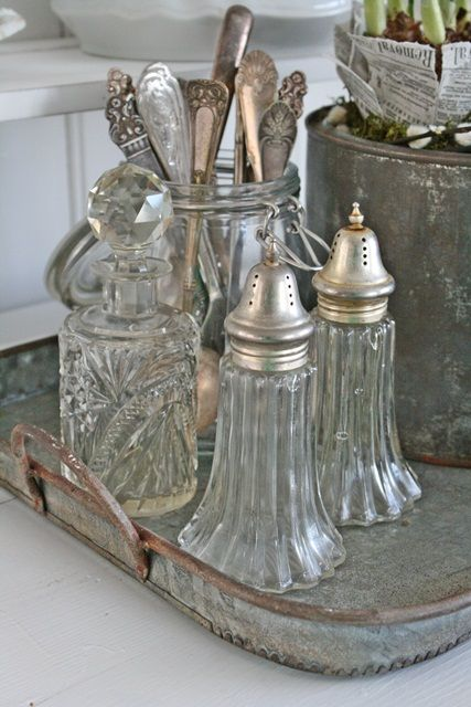 Vintage glass salt and pepper shakers, crystal decanter and silver cutlery.