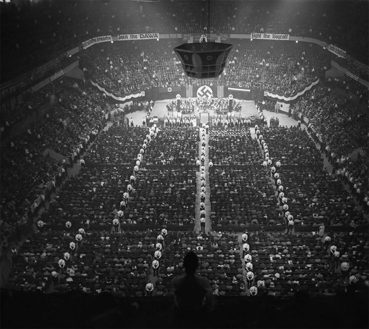 """More than twenty thousand attend a meeting of the German American Bund, which included banners such as """"Stop Jewish Domination of Christian Americans"""". Madison Square Garden, 1939."""