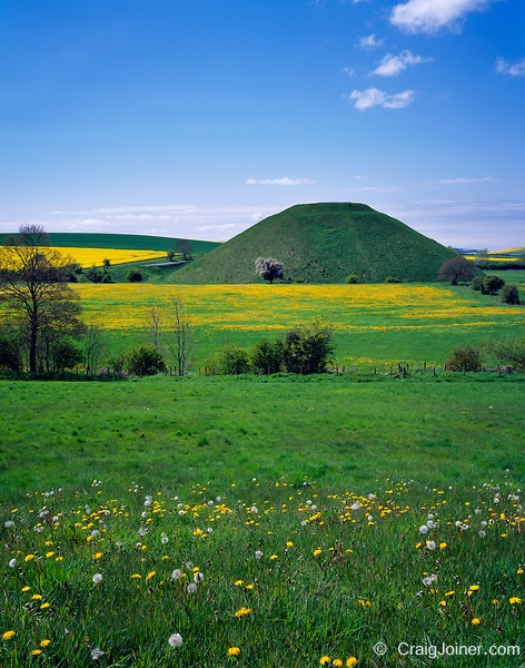 The ancient man made Neolithic chalk mound of Silbury Hill surrounded by fields of dandelions and rapeseed near Avebury, Wiltshire, England, United Kingdom