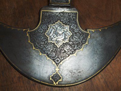 Persian tabar is a single headed axe, in this case from the Qajar dynasty (1795- 1925). This weapon displays an example of silver sheet inlay with chase work creating a bird motif that is surrounded by a floral design chiseled into the blade.