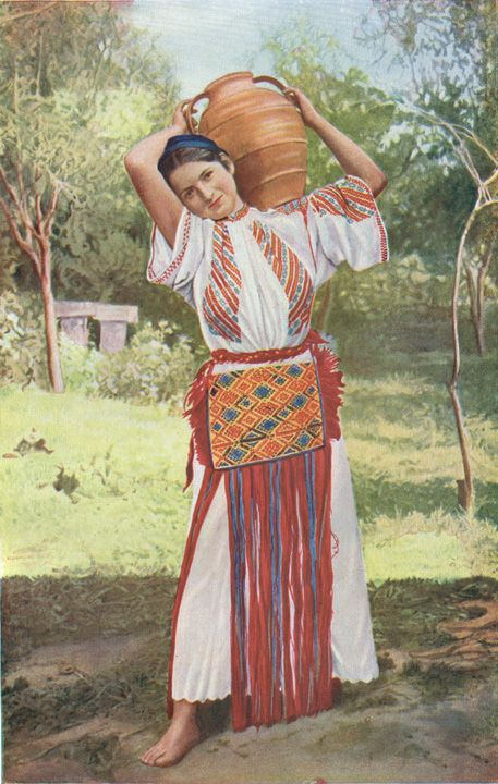 Rumania: Peasant Maiden in Picturesque Attire  In the simple everyday attire of this peasant girl the Rumanian love of lively colours and the native  skill in harmoniously blending them eloquently assert themselves. Photo, Rumaniain Legation