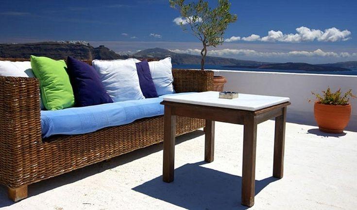 terrazzi moderni grandi con divano in vimini e tavolo in legno