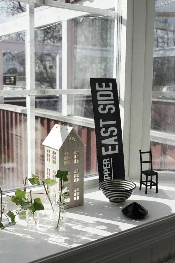 Hus av plåt som inredningsdetalj. Små vaser av glas med kvistar av murgröna. Svart skylt med vit text från Ofelias hus. Svartvit randig skål från allrum. Svart diamant som prydnad i fönstret. Svart liten stol av gjutjärn.