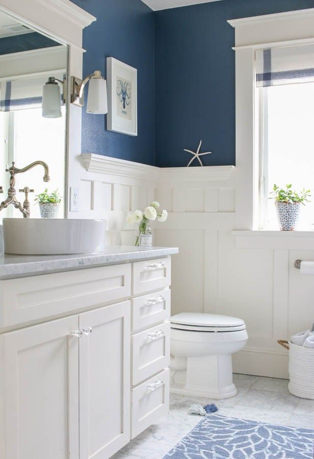 Pretty and fresh navy and white coastal inspired bathroom. Finished with carrara marble and board and batten wainscoting.