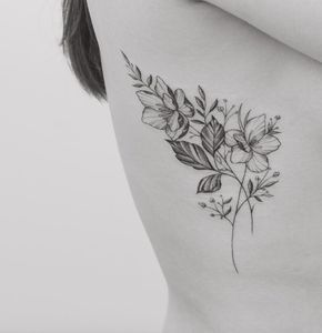 Delicate black and grey ink floral tattoo on rib cage by Tritoan Ly
