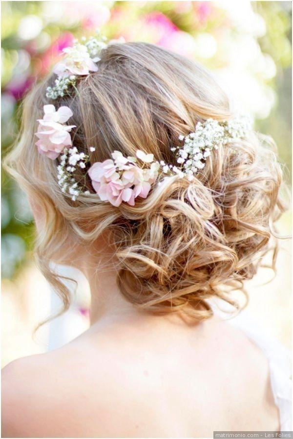 Acconciatura da sposa per capelli raccolti con fiori.