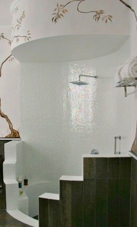 mosaic-tiled with sunken tub and tall circular shower.