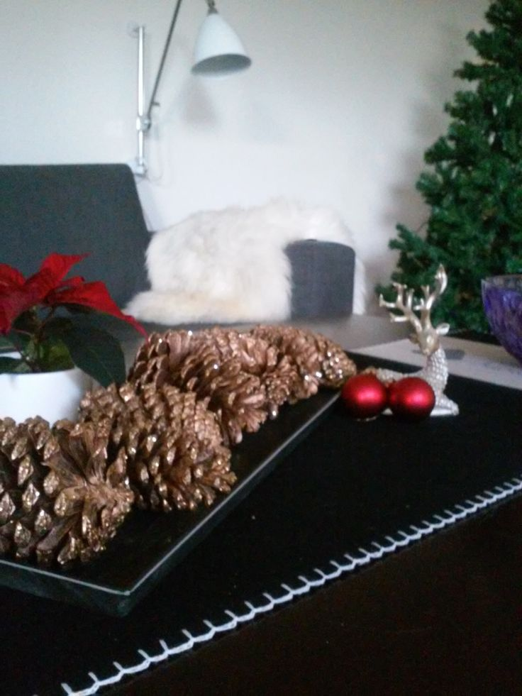 Simple but very Christmassy - arrange some gold sprayed pine cones in the center of your table