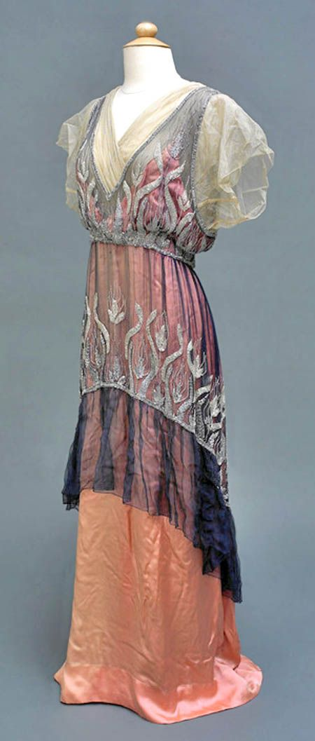 "Fashion ★ ""Dress, Mrs Pialat Delanoue, Paris, ca. 1914. Evening dress of pink silk with blue chiffon over-tunic reaching just below knee level, decorated with sparkling beadware. Fastens at back with hook and eyes."