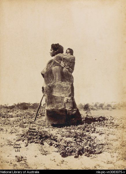 Photo by Samuel White Sweet, 1825-1886. Portrait of unidentified Aboriginal woman wearing a possum skin cloak, carrying a child on her back, South Australia, ca. 1870s?