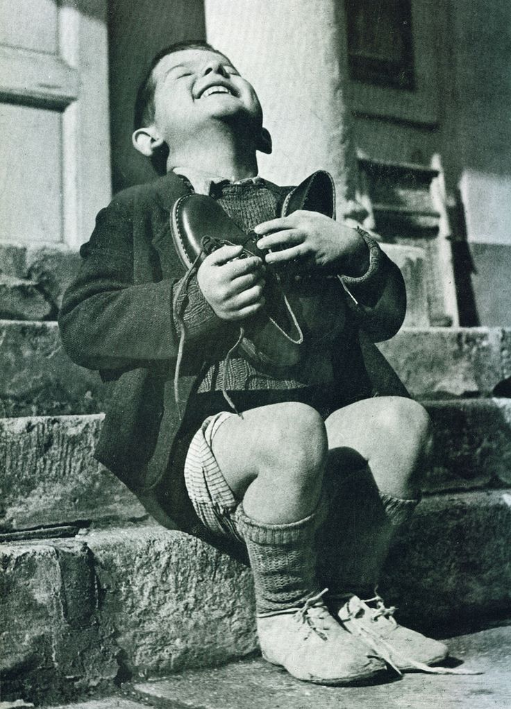 """This photograph entitled """"Werfel's first pair of new shoes,"""" appeared in the 1946 issue of Life magazine. Werfel, a six-year-old Austrian orphan, has just received his first new pair of shoes as part of the post-war relief effort of the American Red Cross."""