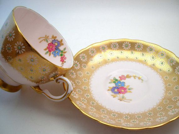 Beautiful tea cup and saucer made by Tuscan England Light pink set with a large gold band with daisies and handpainted center dots. The backstamp date this tea cup from the c: 1947+ The tea cup is 2 3/4 high and the saucer is 5 1/2 diameter The rims, the base and the thumbrest are