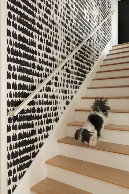 Contemporary staircase with a monochrome wallpaper, creating a striking, modern look.