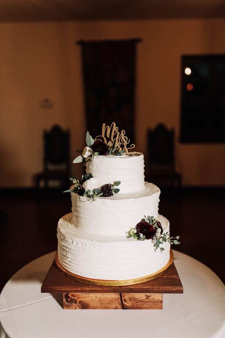 simple and elegant wedding cake with small  flower clusters of white ranunculus, burgundy ranunculus, burgundy scabiosa and eucalyptus with a gold mr. & mrs. topper.