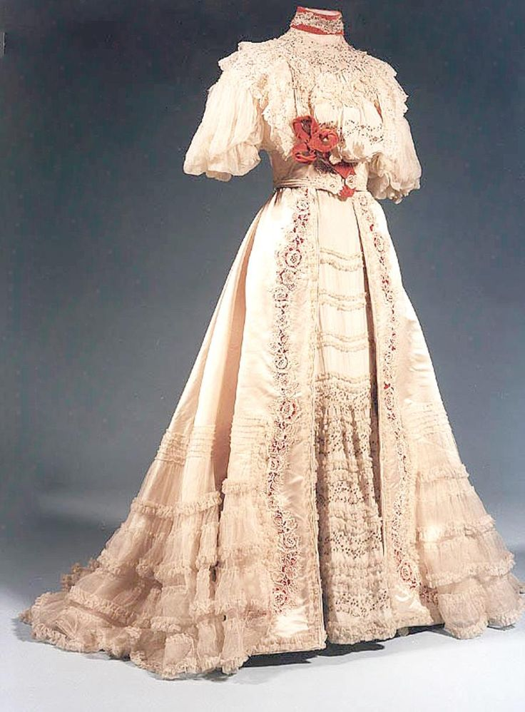 Cream satin, with silk chiffon and crepe de chine trimmed with Honiton and guipure lace, orange velvet and silver sequins. The pouched bodice and flared, trained skirt give the fashionable sweeping curves we associate with the Edwardian age. Title Dress, 1905