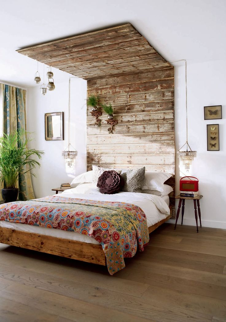 Vintage bedroom with a floating bed base, recycled wood panelled canopy, and hanging bedside chandeliers.
