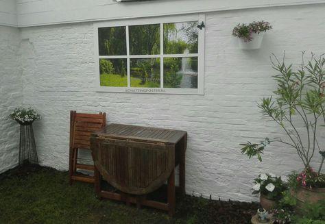 Deze tuinposter met van oorsprong donder houten raamwerk is totaal aan de tuin aangepast door bevestiging van witte houten latten. Super!