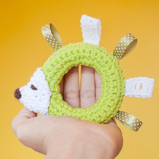 Add ribbon into a crochet ring to make a hedgehog baby toy. Free pattern included.