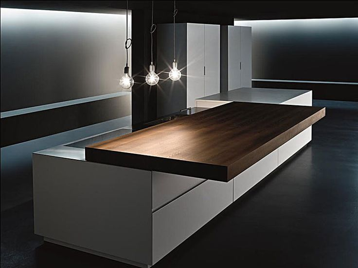 Sliding Top kitchen by American kitchen manufacturer Minimal USA. When closed you have a beautiful interior element. When opened it reveals a stainless steel cooktop and retractable faucet. In this position the sliding top doubles as a lineair table.