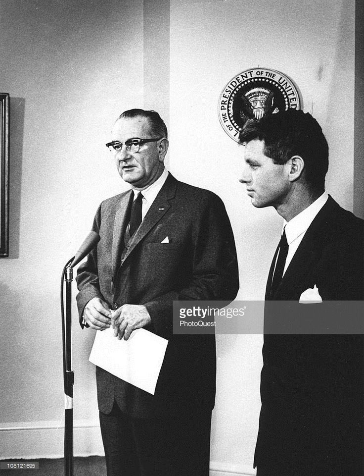 US President Lyndon Johnson (1908 - 1973) (left) speaks into a microphone about United States Attorney General Robert F. Kennedy (1925 - 1968), who had just returned from a tour of South East Asia, Washington DC, January 28, 1964.