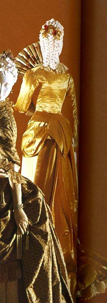 """Платье. Эванс, около 1880. Комплект из корсажа и юбки, золотистый шелковый атлас, корсаж с задрапированной баской и пуговицами, обтянутыми тканью, банты на манжетах, """"пыльная оборка"""" из кружева."""