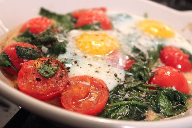 Baked Eggs with Spinach and Tomato Recipe.  Healthy and sounds delicious.  Really have become a fan of the roasted tomato!