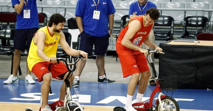 Sergio Llull (e) e Rudy Fernandez, da seleção espanhola de basquete, aproveitam um intervalo dos treinos e brincam com triciclos elétricos