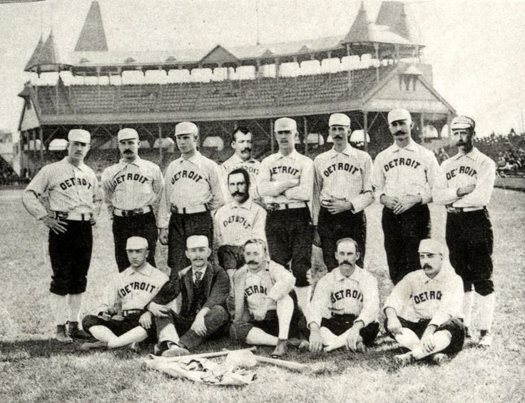 """Two rows of men: one row standing behind a second row seated on the ground. The men are wearing white baseball uniforms with """"Detroit"""" across the chest and white baseball caps."""