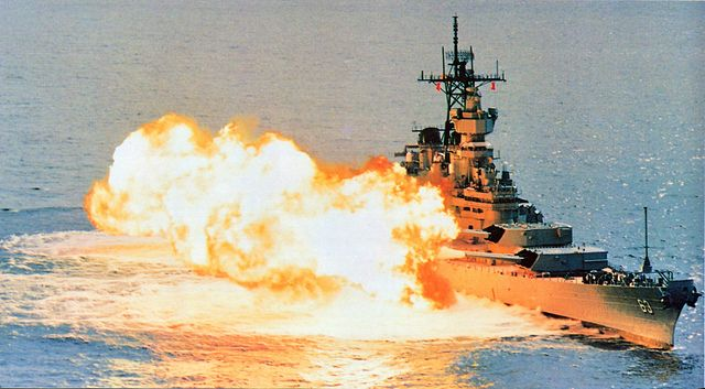 USS Missouri firing a reduced-charge broadside off Sydney, 30 Sept. 1986. Two shells are visible at the left of the picture.