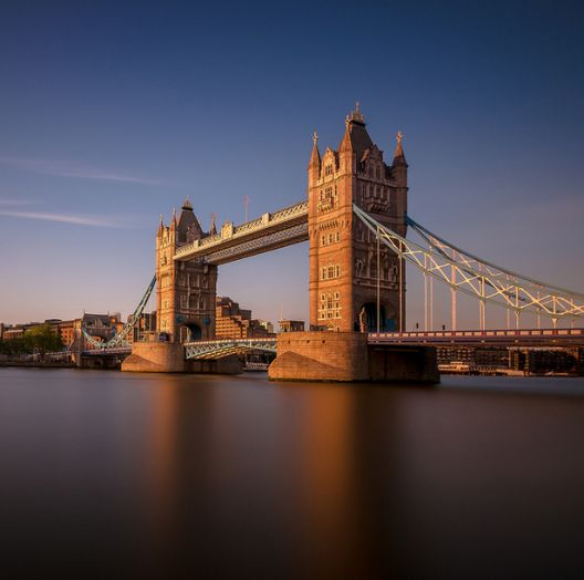 A photo of Tower Bridge over the Thames in London, at dawn.