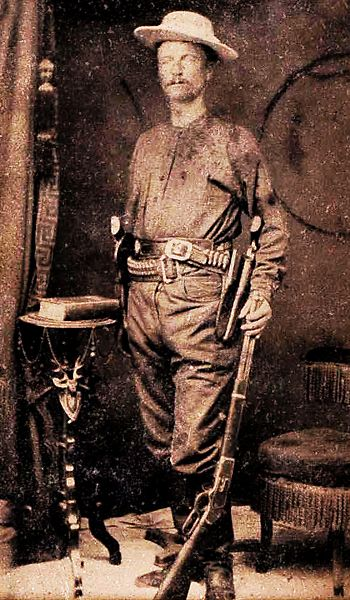 Capt. Junius June Peak in Ranger outfit, holding a Winchester 1873 rifle and wearing two Colt revolvers on holstered cartridge belts