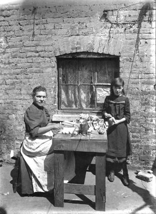 Matchbox-making was dominated by women and children, and was amongst the lowest paid home work available. This woman would paste together strips of paper and wood, called skillets, to form lids and trays. She received 'tuppence ha'penny' per gross (two and a half pence for 144), but had to supply her own paste and fire to dry the boxes. This photograph was taken outside of the workers impoverished dwelling, where they would normally spend up to 12 hours working every day. ca 1900.