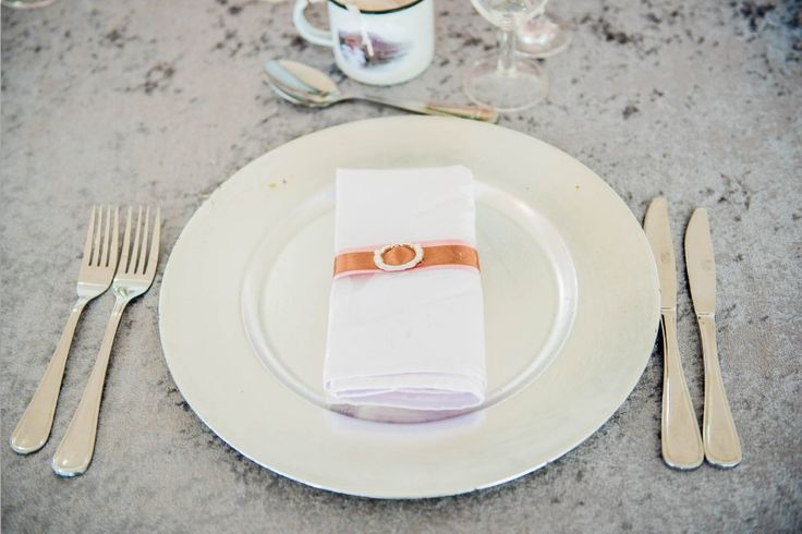 Monte Vista Venue silver under plates with a plain white napkin, pink and brown ribbon with a buckle tied around the napkin for a pink and brown wedding