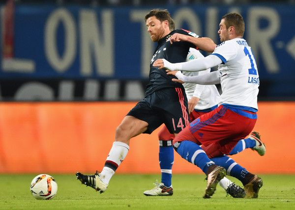 Xabi Alonso of Bayern Munich holds off Pierre-Michel Lasogga of SV Hamburg during the Bundesliga match between Hamburger SV and FC Bayern Muenchen at Volksparkstadion on January 22, 2016 in Hamburg, Germany.