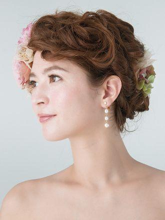 ニュアンスカラーのコサージュで個性派のセレモニースタイルに ウェディングドレス・カラードレスに合う〜アップの花嫁衣装の髪型まとめ一覧〜