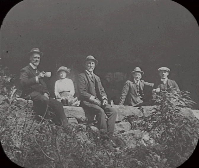 Title: Group at King's Cave, Linden Date & Location: 6 September 1912, Linden (NSW) Description: Black and white glass lantern slide. Title in ink on upper edge label Notes: Group portrait of members of Royal Australian Historical Society sitting on rock ledge, taken during excursion to King's Cave, Linden. Frank Walker on left, holding teacup. From negative in Mitchell Library Frank Walker Collection ON 150, Item 968A.
