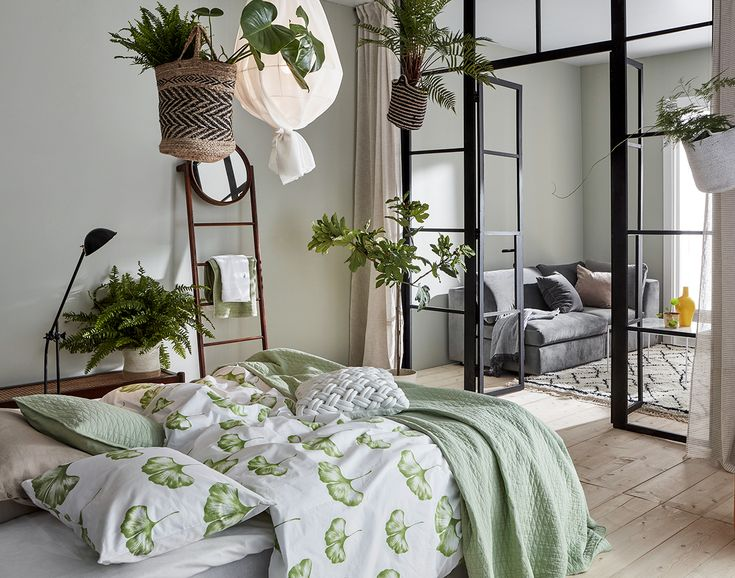 Bedroom with industrial glass wall, green bedding and green plants. Ideas how to decorate with the biggest trends 2018.