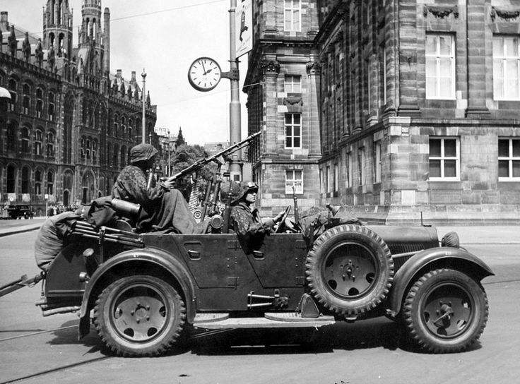 """Members of the German Waffen-SS Panzergrenadier Regiment 4 """"Der Führer"""" Division, SS-Verfügungsdivision (SS Dispositional Troops) drive through Amsterdam near the Royal Palace in a Wanderer W11 after the capitulation of Dutch forces. Amsterdam."""